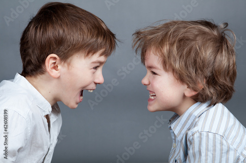 Portrait of two happy brothers on agray background