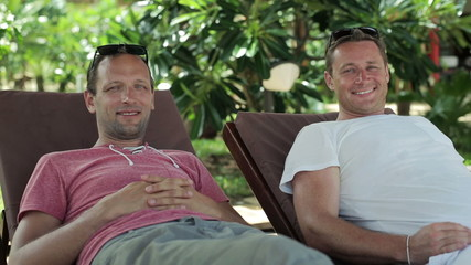 Two happy male friends relaxing on sunbeds