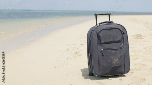 Travel valise on exotic beautiful beach