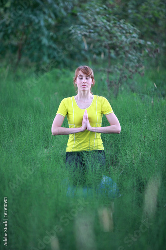 pretty woman meditating in yoga pose in nature