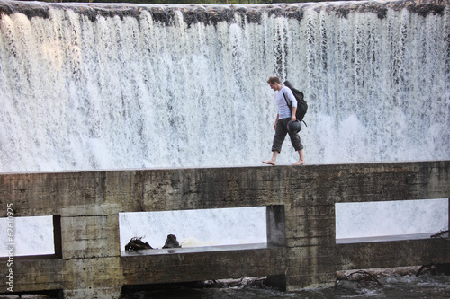 Fit man with ball backpack on footbridge at the waterfall