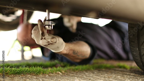 Car mechanic unscrewing components under a car