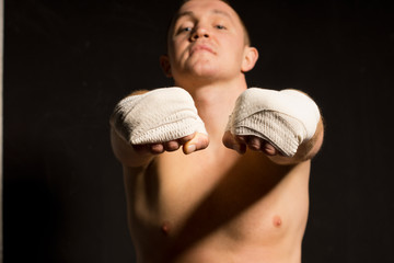 Young boxer extending both fists at the camera