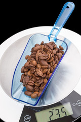 Scoop of coffee beans on the scales