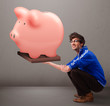 Handsome man holding a huge savings piggy bank