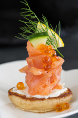 Appetizer with smoked salmon and sour cream, garnished with dill