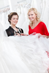 Two girls drink spirits while discussing wedding gown