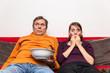 Vater und Tochter sitzen geschockt auf der Couch