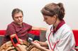 Altenpflegerin misst Blutdruck bei Senior