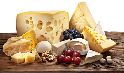 Different types of cheese over old wooden table.