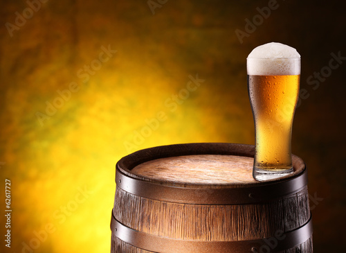 The glass of beer over woden barrel.