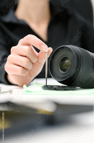 woman engineer repairing camera lens