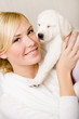 Woman keeping white puppy of Labrador