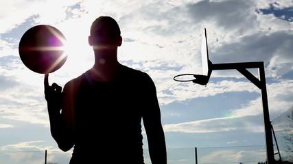 Basketball player silhouette spinning the basketball