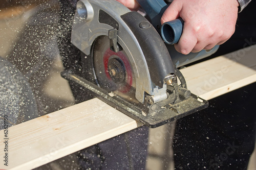 Man is working with electric circular saw
