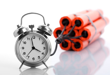 Alarm clock and dynamite on white