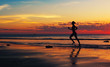 Silhouette of woman runing  along the sea coast