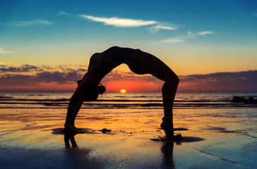 Women exercising on the beach at sunset