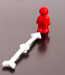 Red toy man and arrow on glossy background