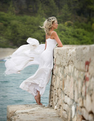 Young, beautiful and sexy woman, white dress, strong wind blows