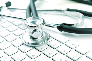 Medical stethoscope lying on laptop keyboard