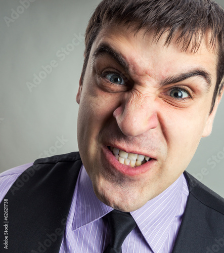 Businessman making faces closeup image