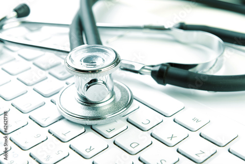 Medical stethoscope lying on laptop keyboard