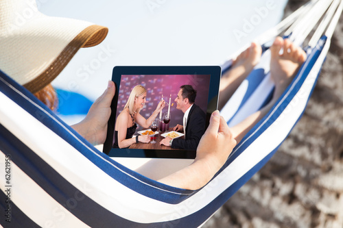 Woman Watching Movie On Digital Tablet In Hammock