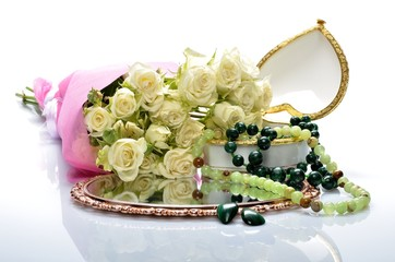 Women's jewelry and a bouquet of flowers in still life