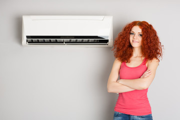 Beautiful red haired girl and air conditioner