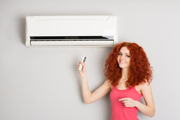 Red haired girl holding a remote control air conditioner