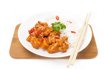 Chinese food - chicken in tomato sauce, sesame seeds and rice