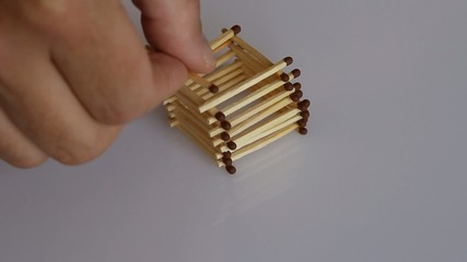 Human hand builds a stylized house out of matchsticks. Time laps