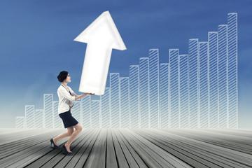 Businesswoman carrying upward arrow