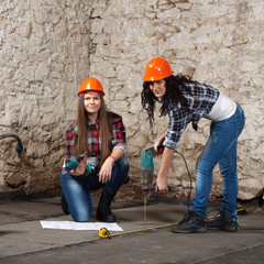 Two young long-haired woman with a drill and screwdriver
