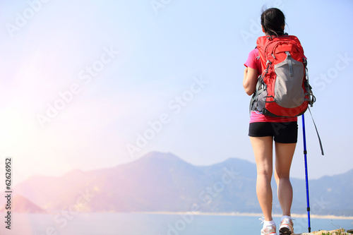 hiking woman stand seaside mountain peak rock