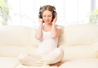 beautiful girl in headphones enjoying music at home on the couch