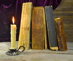 Old books with burning candle