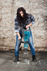Young long-haired woman with a jackhammer