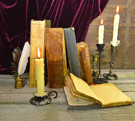 Open diary with old books and candles