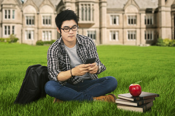 Male student using mobilephone outdoor