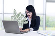 Shocked businesswoman looking money at laptop