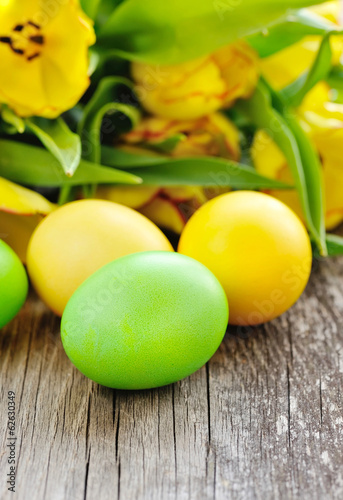 Easter eggs with tulips on old wooden table
