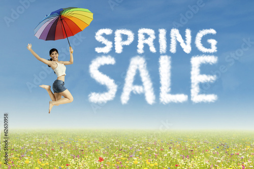 Woman jumping with spring sale clouds