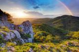 Green mountain with rainbow