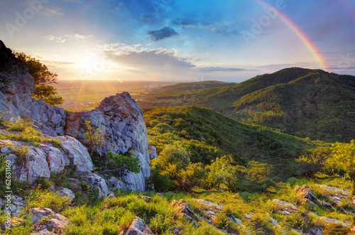 Green mountain with rainbow