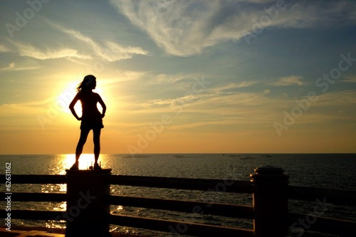 silhouette of woman standing at the sea