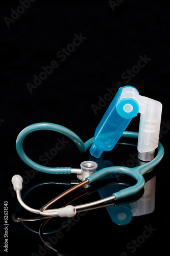 Stethoscope and inhaler isolated on  black background.