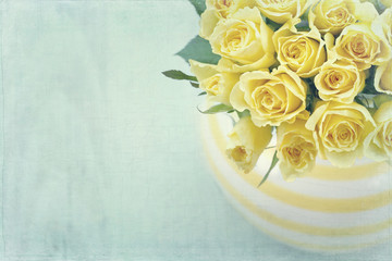 Striped vase with a bouquet of yellow roses