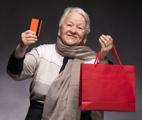 Happy old woman with shopping bags and credit card